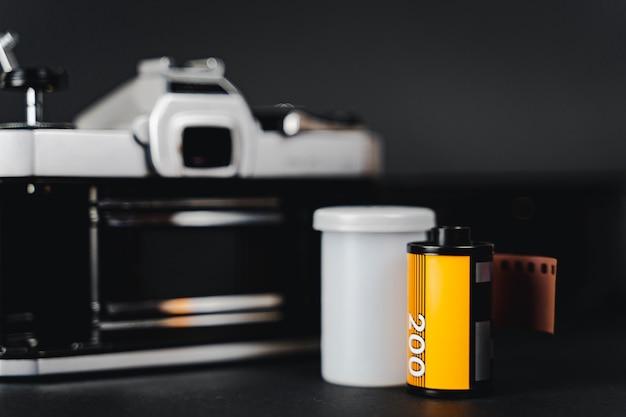 Alte slr-filmkamera und eine filmrolle auf schwarzem hintergrund, fotografie-konzept.