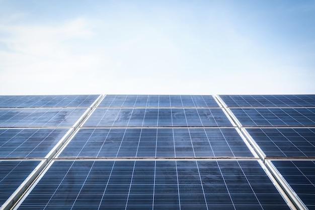 Alte sonnenkollektoren vor blauem himmelshintergrund, anordnung von solarenergieanlagen oder sonnenkollektoren wartungstechniker-konzept