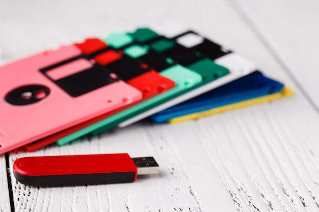 Alte speicherdiskette auf holztisch gegen usb-diskettentreiber