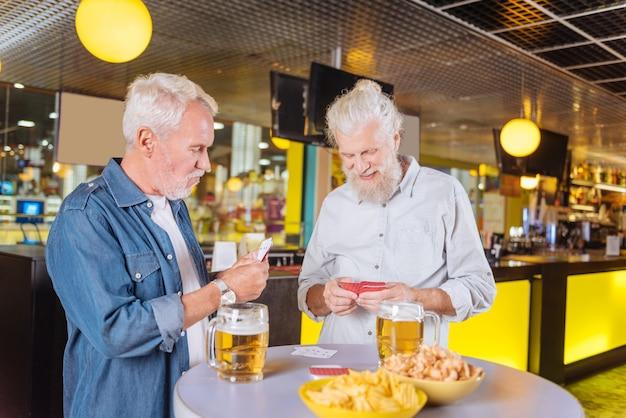 Alte spieler. freudige glückliche männer, die karten spielen, während sie sich in der kneipe treffen