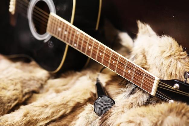 Alte staubige akustische cutaway-gitarre auf dem boden. dreadnought-akustikgitarre aus fichte. gitarre auf pelzhintergrund.