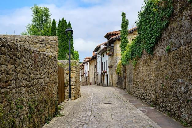 Alte steinerne dorfstraße mit mauern, die mit grün und blumen bedeckt sind