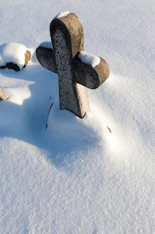 Alte steinkreuze in der wintersaison, religiöse kreuze im schnee in der wintersaison