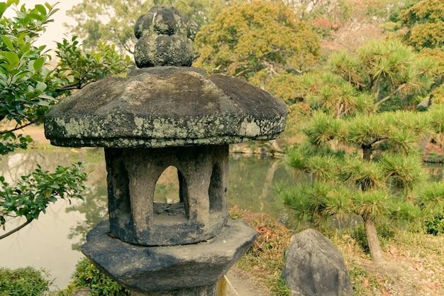 Alte steinlaterne im traditionellen japanischen zengarten in kyoto, japan; fokus auf laterne