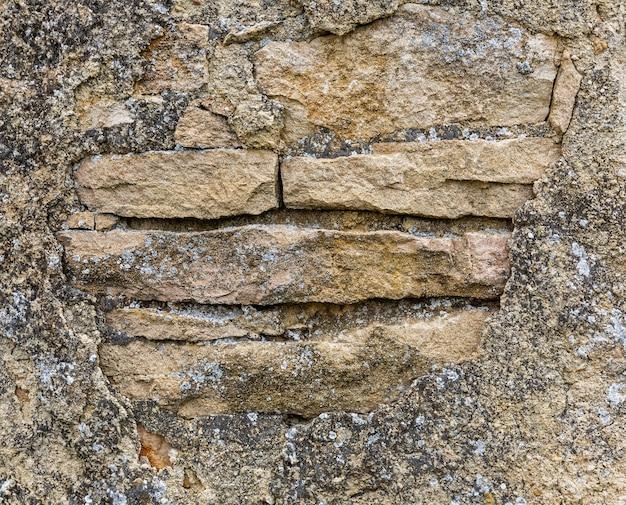 Alte steinmauer mit bröckelndem gips