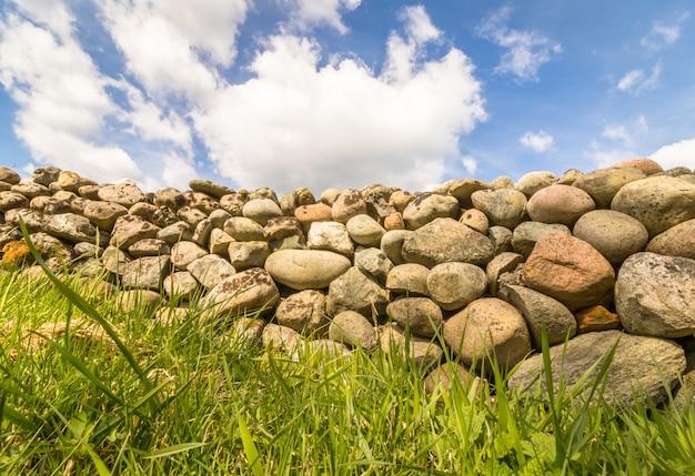 Alte steinmauer mit grünem gras vorne und blauem himmel mit wolken oben