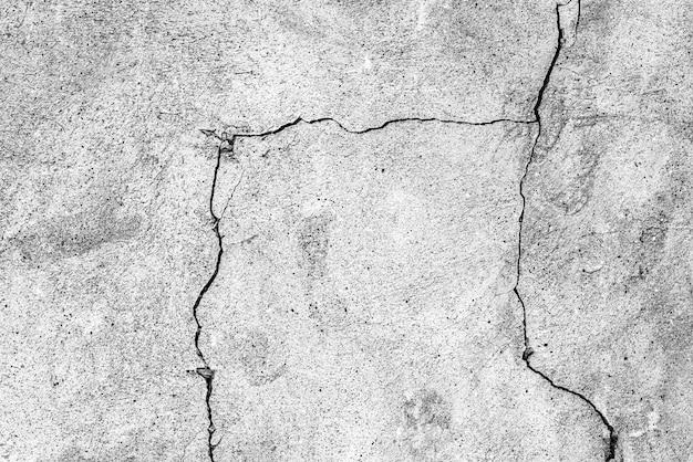 Alte steinmauer mit riss, strukturiertem schwarzweiss-hintergrund