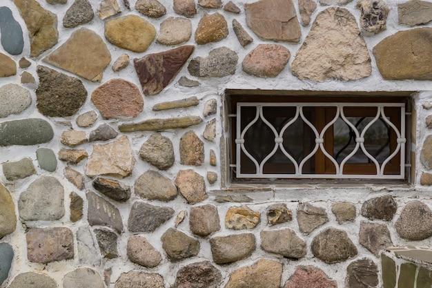 Alte steinmauer und weißes gitter auf einem fenster.