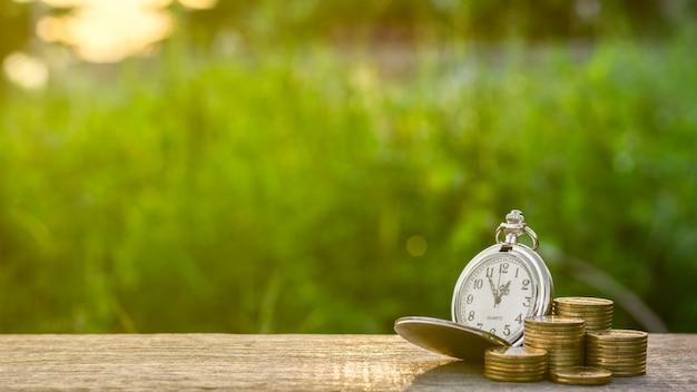 Alte taschenuhr und ein stapel goldene münzen