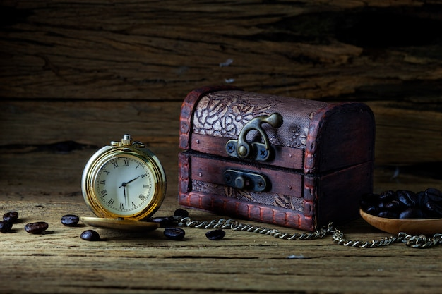 Alte taschenuhr und schatztruhe auf dunklem holz, stillleben