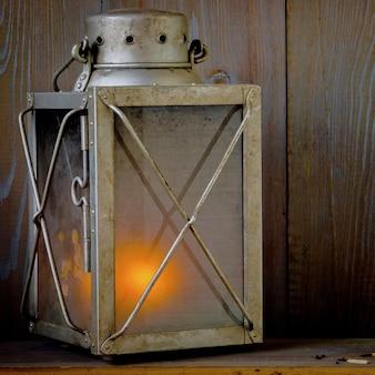 Alte tragbare lampe mit einer brennenden kerze