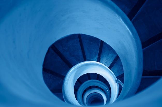 Alte treppe in wendeltreppe in klassischer blauer farbe des jahres 2020 getönt