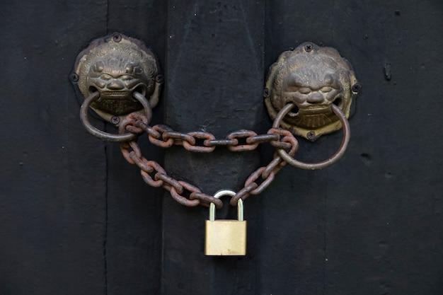 Alte tür mit einem löwenkopfklopfer werden durch eine alte kette und ein vorhängeschloß verschlossen.