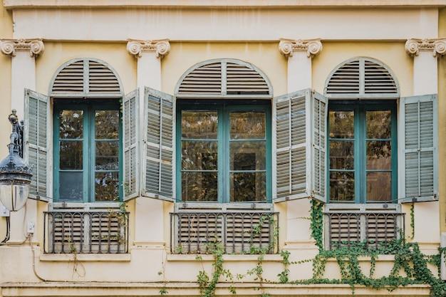 Alte türkisfarbene fenster eines wohnhauses im neoklassizistischen stil