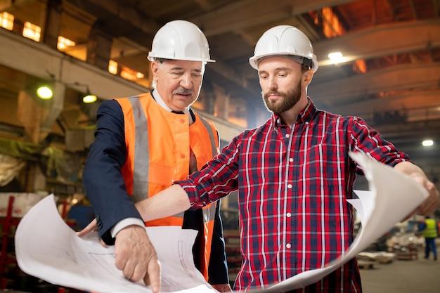 Alte und junge bauherren oder ingenieure diskutieren beim arbeitstreffen in einer industrieanlage über baupläne