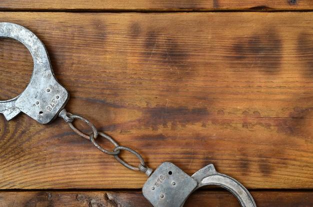 Alte und rostige polizeihandschellen liegen auf einer verkratzten holzoberfläche