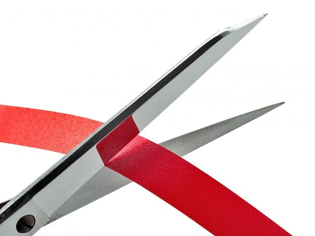 Alte und rostige scheren, die ein rotes band schneiden. beschneidungspfad