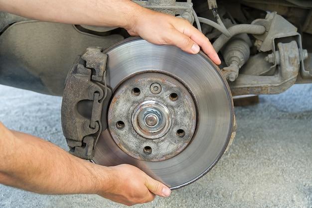 Alte und schmutzige hintere kipppause des fahrzeugs zur reparatur. bremsen an einem auto mit abgenommenem rad. detailbild von autos brechen baugruppe vor reparatur.