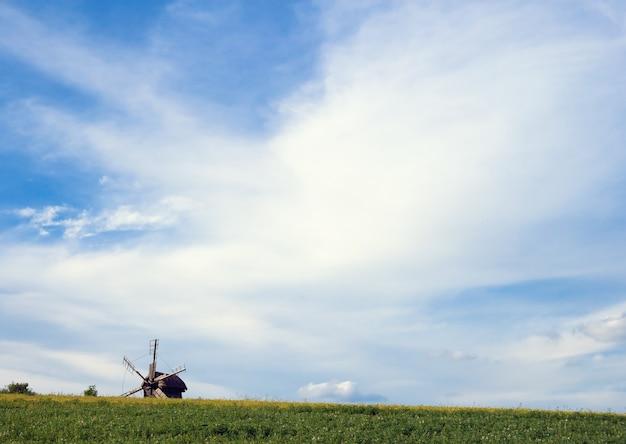 Alte veraltete windmühle jenseits des hügels auf feld