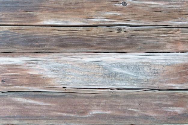 Alte verwitterte braune und weiße holzoberfläche mit langen brettern ausgerichtet.