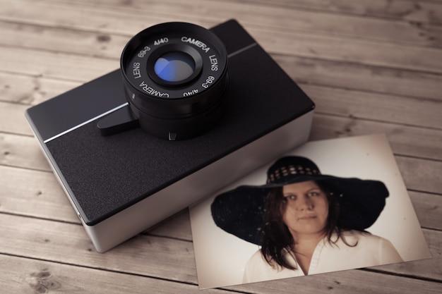 Alte vintage fotokamera mit wooman portrait auf einem holztisch. 3d-rendering