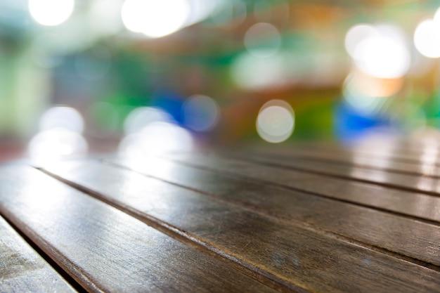 Alte vintage grungy braune hölzerne tischplattenbretter mit unscharfem hellem hintergrund der restaurantbar cafe: grunge gealtertes holz mit verschwommenem warmem cremefarbenem hellem bokeh-hintergrund