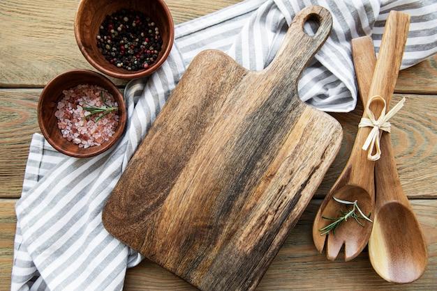 Alte vintage küchenutensilien. holzlöffel, schneidebrett, serviette und gewürze über weißem holztisch. draufsicht
