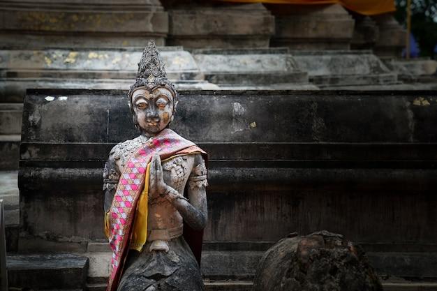 Alte vintage scaried stone buddhismus statue; leuchtend gelbes auge, hebt die hand und kniet auf der bühne, schaut auf den boden. chiangrai, thailand.