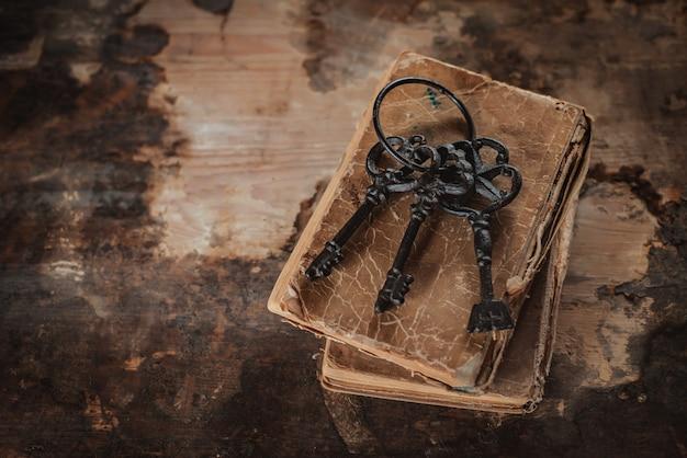 Alte vintage-schlüssel auf einem alten ramponierten buch