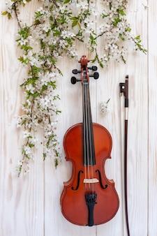 Alte violine mit geigenbogen und blühenden kirschbaumasten