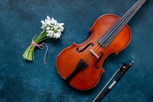Alte violine und frischer schöner strauß der ersten frühlingswaldschneeglöckchen