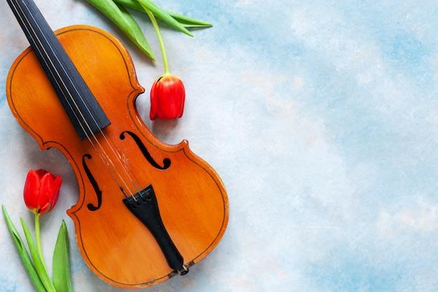 Alte violine und zwei rote tulpen.