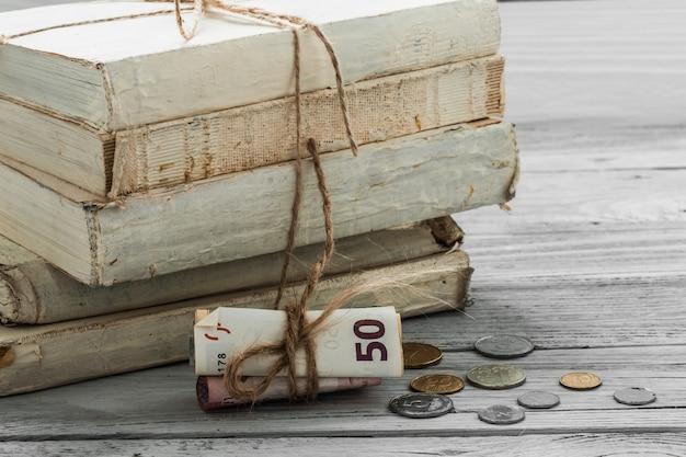 Alte weiße bücher mit geld und münzen auf hölzernem hintergrund