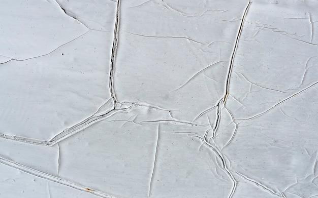Alte weiße geschälte gipswand mit rissigem strukturrahmen leerer schmutzhintergrund. graue backsteinmauer mit schäbiger stuckschicht isoliert. renovierungskonzept. leere geschälte oberfläche