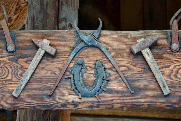 Alte werkzeuge an ein holzbrett genagelt. ausstellung