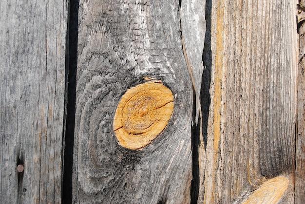Alte, zeitgeschwärzte planken mit gelben knoten teer, erleuchteten die frühlingssonne