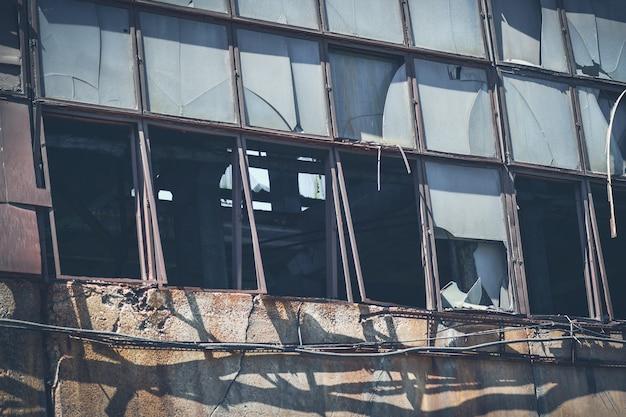 Alte zerbrochene fenster in einer verlassenen fabrik.