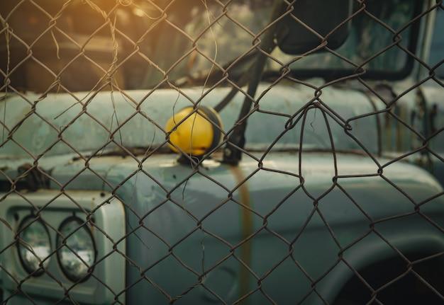 Alte zerstörte lastwagen in schwarzweisszene. verlassener rostiger lastwagen im drahtzaun. verfallener verlassener lkw. blick vom zaun zum lkw.