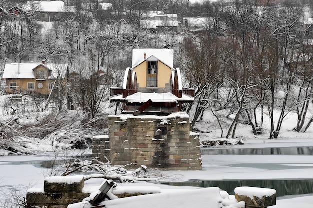Alte zerstörte stahlstraßenbrücke über fluss nach schneefall