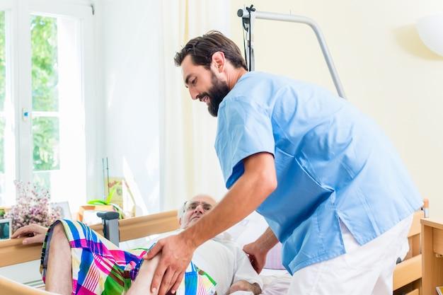 Altenpflegerin, die älterem mann von rollstuhl zu bett hilft