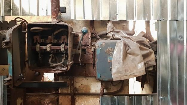 Alter abgebauter und rostiger elektrischer schild in einer verlassenen fabrik vor dem hintergrund des chaos.