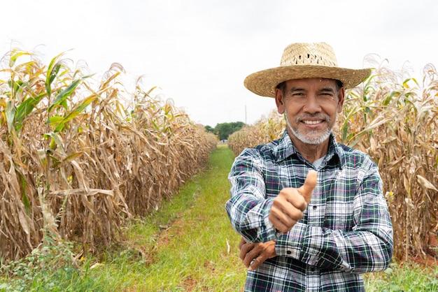 Alter älterer landwirt mit dem weißen bartdaumen, der sich oben überzeugt fühlt