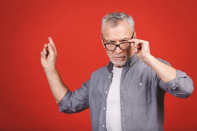 Alter älterer mann, der brille trägt, während mit hand präsentiert und mit finger zeigt.