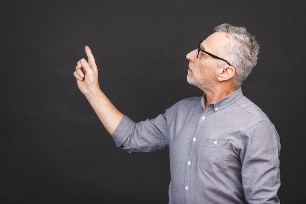 Alter älterer mann, der eine brille trägt, die gegen schwarze wand isoliert ist, erstaunt und lächelnd, während er mit der hand präsentiert und mit dem finger zeigt.