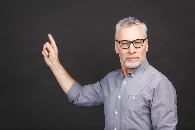 Alter älterer mann, der eine brille trägt, die gegen schwarze wand isoliert wird, staunte, während er mit hand präsentierte und mit finger zeigte.