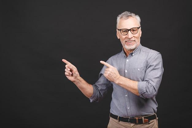 Alter älterer mann, der eine brille trägt, die gegen schwarzen hintergrund lokalisiert wird, erstaunt und lächelnd, während sie mit hand präsentiert und mit finger zeigt.