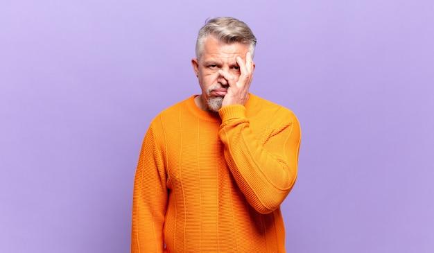 Alter älterer mann, der sich nach einer ermüdenden, langweiligen und mühsamen aufgabe gelangweilt, frustriert und schläfrig fühlt und das gesicht mit der hand hält