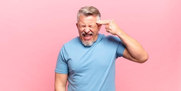 Alter älterer mann, der unglücklich und gestresst aussieht, selbstmordgeste, die waffenzeichen mit der hand macht und auf den kopf zeigt