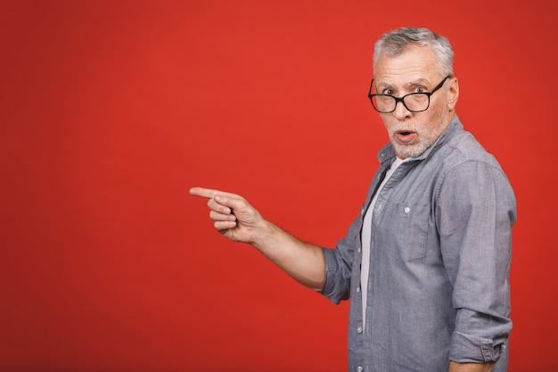 Alter älterer mann mit brille erstaunt und schauend, während er mit der hand präsentiert und mit dem finger zeigt.