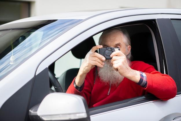 Alter älterer mann mit grauem bart sitzt im auto und macht ein foto mit einer vintage-fotokamera